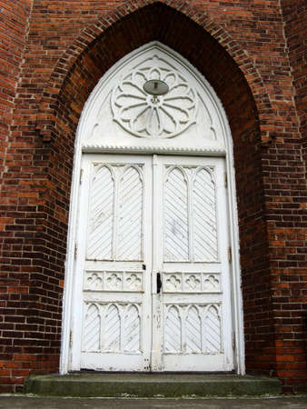 dogma: A white church door surrounded by a stained dark wall.
