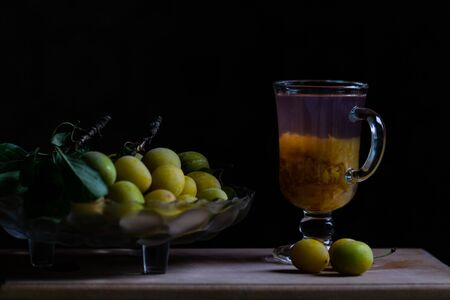Still life with fresh yellow plums and glass of home made plum limonade, backlight, black background