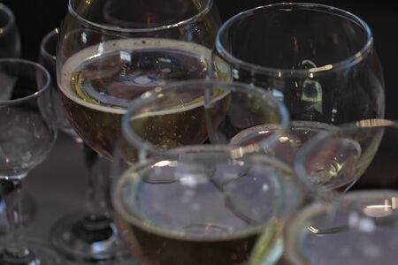 Glasses with white wine, selective focus, dark background