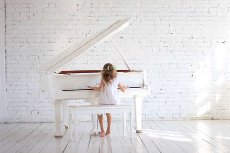 Girl in white dress playing piano in white hall with briks wall, copy space 写真素材