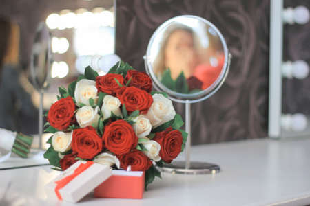 marriage rings in box with red and white roses, mirror with blured bride reflection, selective focus 版權商用圖片