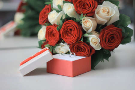 A close up marriage rings in box with red and white roses, horizontal orientation 版權商用圖片