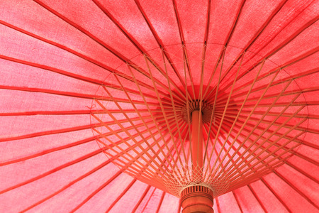 Under of a vintage red Thai umbrella Stock Photo