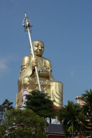 bodhisattva:  Big golden Bodhisattva statue with blue sky at Hatyai