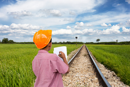 The way of train through the wide green fields of the countryside. photo