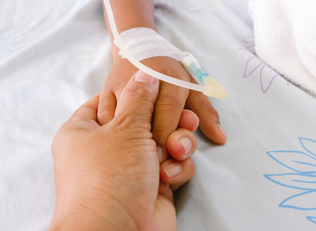 mother holding childs hand who fever patients have IV tube.