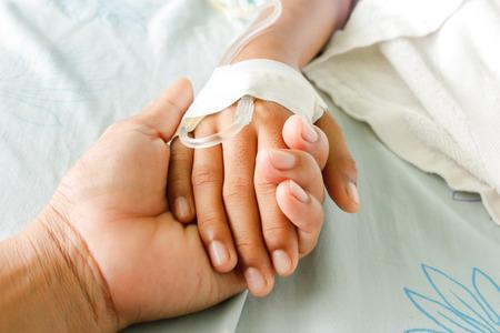 bebe enfermo: madre sosteniendo la mano de niño que los pacientes con fiebre tienen tubo IV.