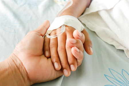 sick: mother holding childs hand who fever patients have IV tube.