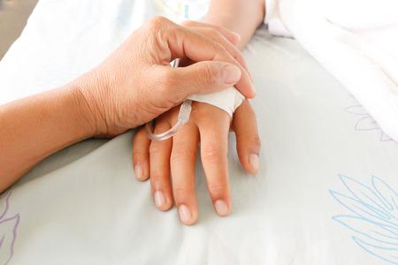 pacientes: madre sosteniendo la mano de ni�o que los pacientes con fiebre tienen tubo IV.