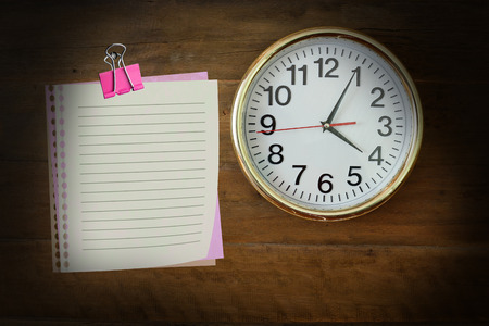 o'clock: The paper  with four oclock hanging on the wooden wall. Stock Photo