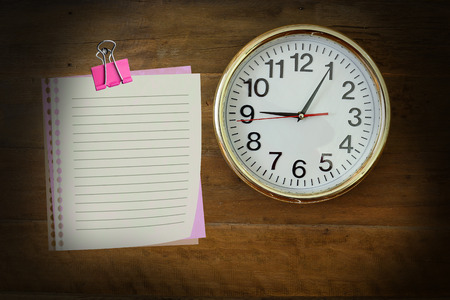 o'clock: The paper  with nine, oclock hanging on the wooden wall. Stock Photo