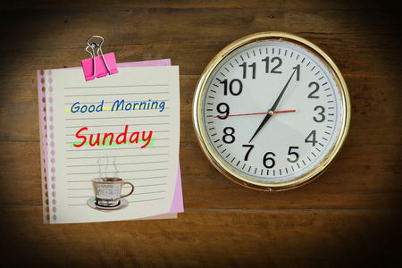 seven o'clock: The paper wrote Good Morning Sunday with seven oclock hanging on the wooden wall.