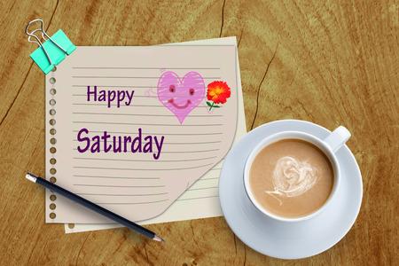 幸せな土曜日の単語とコーヒー カップの木製の背景に。