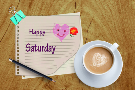 Happy Saturday word and coffee cup on wooden background.