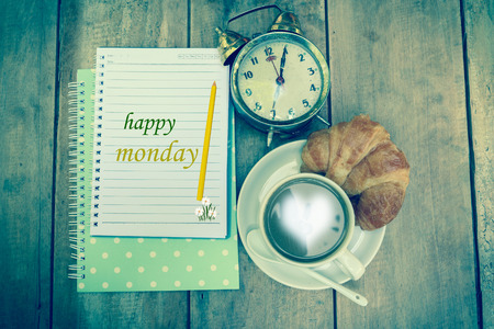 Happy Monday word and coffee cup on vintage wooden background. Zdjęcie Seryjne
