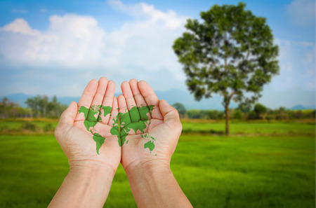 world map in hand on green field natural background.