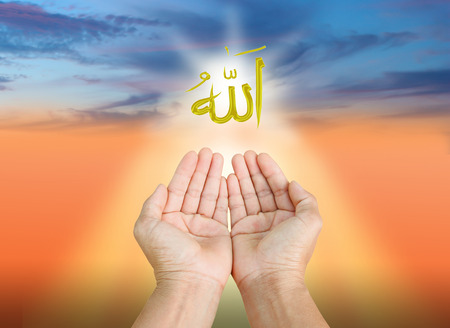 Hands of man praying to allah god of Islam on a sunset.The words spell is Allah means the God of Islam.