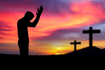 knelt: Silhouette man  praying over the cross on beautiful sunset