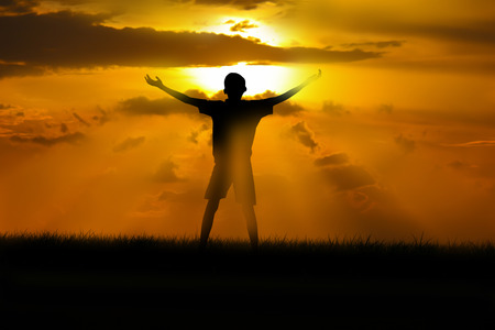 Boy standing arms out stretched at sunset. Imagens