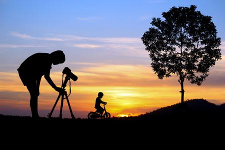 orange sunset: Photographer girl with little boy at orange sunset.