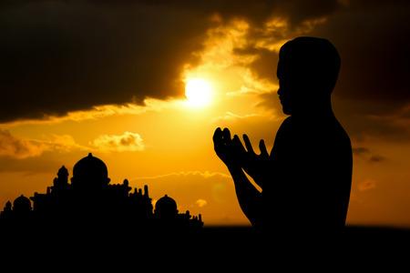 Silhouette muslim people  praying at sunset.