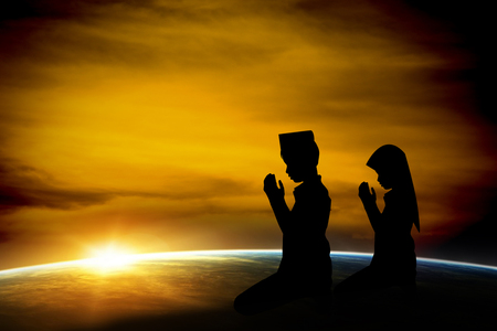 muslim: Silhouette muslim boy and girl praying at sunset.  Stock Photo