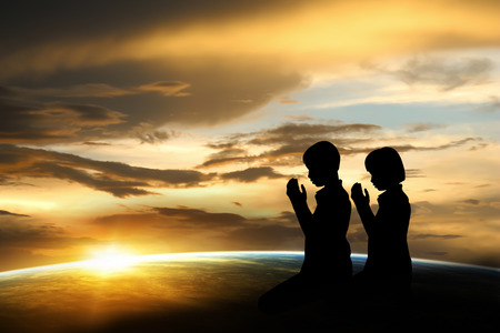 Silhouette  boy and girl praying at sunset.  Banco de Imagens