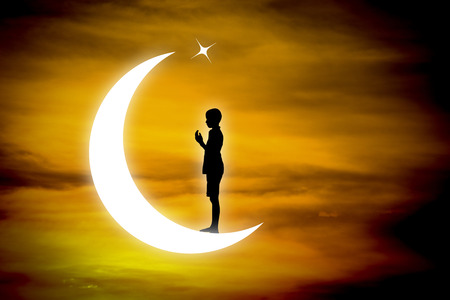 devout: Silhouette muslim boy praying at night with moon background. Stock Photo