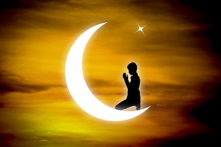 orando: Silueta del muchacho musulmanes orando en la noche con la luna de fondo.