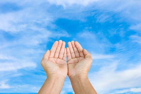 manos orando: dos mano vacía en el cielo azul Foto de archivo