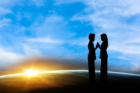 femmes muslim: Silhouette garçon et une fille musulmane au coucher du soleil.