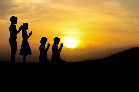 orando: personas que rezan en la puesta del sol. Foto de archivo