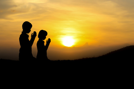 christian faith: people  praying at the sunset. Stock Photo
