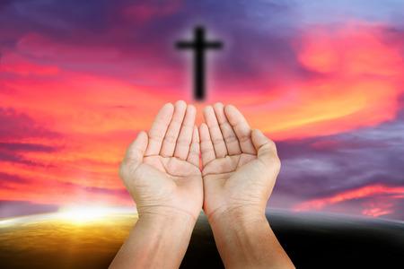 mano de dios: personas que rezan en la puesta del sol. Foto de archivo