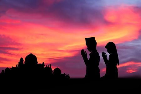 Silhouette muslim people  praying at sunset.