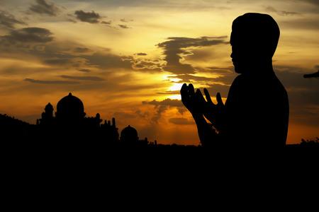 シルエット夕日に祈るイスラム教徒の人々。