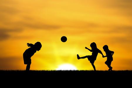 jugando futbol: tres hermanos chicos juegan al atardecer.