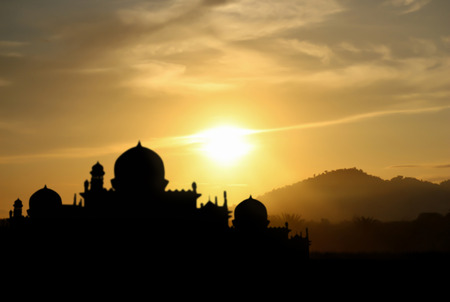 namaz: A silhouette of a mosque sunset background