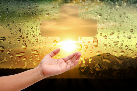 beautiful jesus: women hand touch the cross and pray at water drops on sunset mirror background.