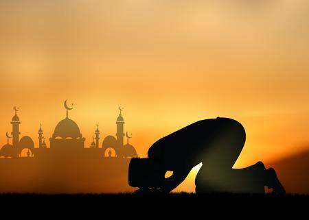 personas orando: Silueta de las personas musulmanas rezando en la puesta del sol. Foto de archivo