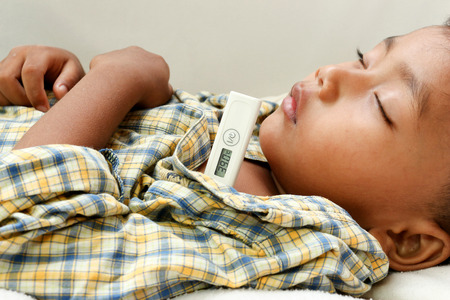 coronavirus: a little boy who has fever.focus at a temperature.