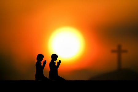 people  praying at the sunset. Stock Photo
