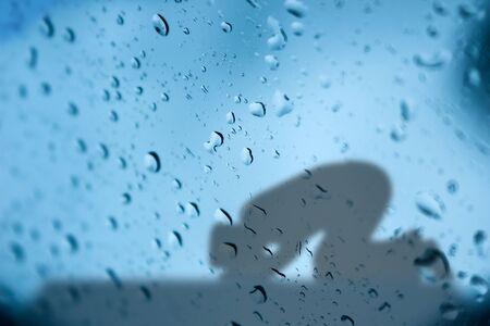 looking at mirror: Islamic man praying looking through water drops on mirror background
