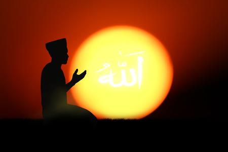 allah: man praying to allah god of Islam on sunset.The words spell is Allah means the God of Islam.
