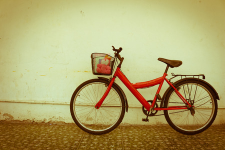 dirty house: red bicycle on old dirty  house wall,vintage style.
