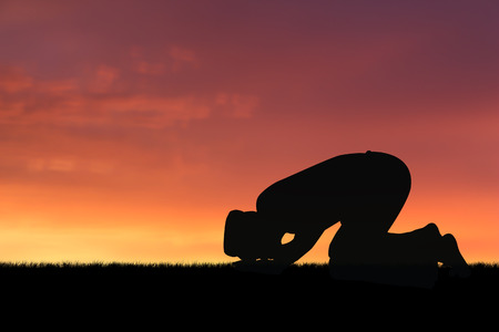 islamic pray: man praying to allah god of Islam on sunset.