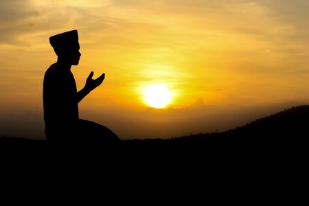 hombre orando: hombre rezando a Al� dios del Islam en la puesta del sol.