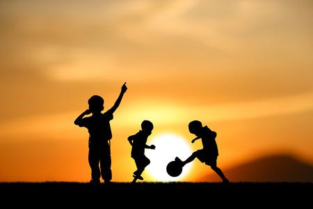 niño corriendo: hermanos silueta, los niños juegan al fútbol en la puesta del sol.