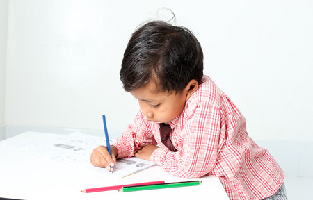 drawing cartoon: little boy drawing cartoon with crayons.