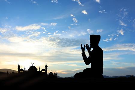 nene y nena: Silueta de la gente musulmanes rezando en la puesta del sol